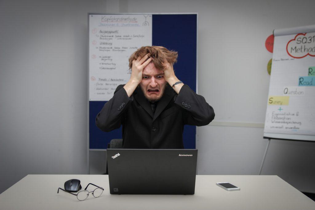 PCの前で頭を抱える男性